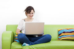 Full length of happy young woman using laptop while sitting on green sofa Stock Photo