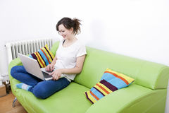 Full length of happy young woman using laptop while sitting on green sofa Stock Photos