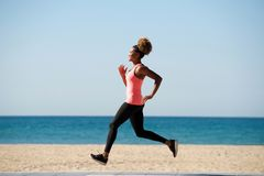 Full length healthy african woman running along the beach in morning. Full length side portrait of healthy african woman running along the beach Royalty Free Stock Images
