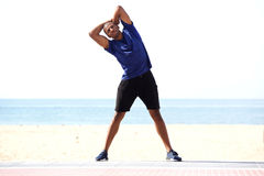 Full length healthy black man stretching in morning on beach Royalty Free Stock Image