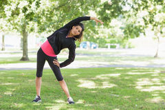 Full length of a healthy woman doing stretching exercise in park Royalty Free Stock Images