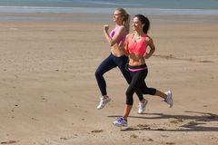 Full length of healthy women jogging on beach Royalty Free Stock Photo