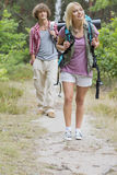 Full length of hiking couple in forest Royalty Free Stock Photography