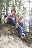 Full length of hiking couple sitting on edge of cliff in forest Stock Images