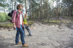 Full length of hiking couple walking in forest Stock Photography