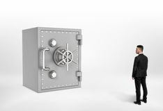 Full length illustration of businessman looking at the huge steel safe. Stock Photo