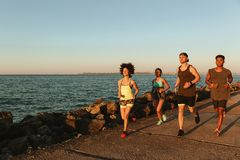 Full length image of four sports people running outdoors Stock Image