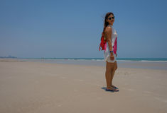 Full length image of model looking over shoulder on beach clear blue sky. Stock Image