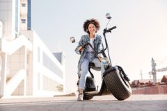 Full length image of Smiling curly girl sitting on motorbike Royalty Free Stock Photos