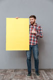 Full length image of Smiling man holding blank board. Full length image of Smiling man in shirt holding blank board and showing thumb up. Isolated gray Stock Photography