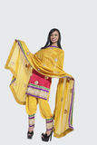 Full length of an Indian woman in salwar kameez standing over gray background Royalty Free Stock Images