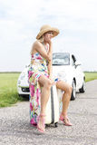 Full length of irritated woman sitting on luggage by broken down car Stock Photography