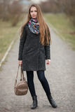 Full length lifestyle portrait of young and pretty adult woman with gorgeous long hair posing in city park with shallow depth of f. Ield in grey coat, hat, scarf royalty free stock photos