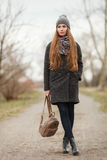 Full length lifestyle portrait of young and pretty adult woman with gorgeous long hair posing in city park with shallow depth of f. Ield in grey coat, hat, scarf stock photo