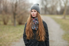 Full length lifestyle portrait of young and pretty adult woman with gorgeous long hair posing in city park with shallow depth of f. Ield in grey coat, hat, scarf stock image