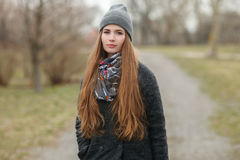 Full length lifestyle portrait of young and pretty adult woman with gorgeous long hair posing in city park with shallow depth of f. Ield in grey coat, hat, scarf royalty free stock photography