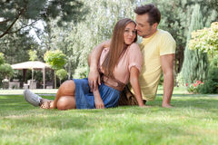Full length of loving young couple relaxing on grass in park Royalty Free Stock Photography