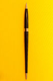 Full length luxury pen on yellow background Stock Photography