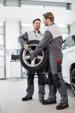 Full length of maintenance engineers carrying tire in car workshop Royalty Free Stock Photography