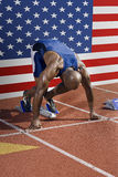 Full length of male athlete ready to race with American flag in background Royalty Free Stock Images