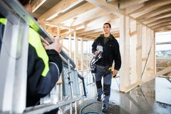 Carpenter Holding Drill Machine While Looking At Colleague Carry Stock Image