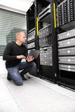 Male Consultant Using Laptop While Monitoring Servers In Datacen. Full length of male IT consultant using laptop while monitoring servers in datacenter Royalty Free Stock Image