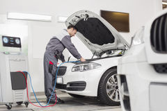 Full length of male engineer examining car in automobile repair shop Royalty Free Stock Photos