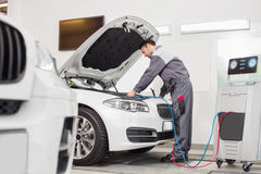 Full length of male engineer examining car in automobile repair shop royalty free stock images