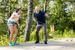 Friends Screaming While Picking Wooden Block With Ropes. Full length of male and female friends screaming while picking wooden block with ropes on patio in Stock Photography