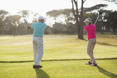Full length of male golf player teaching woman Royalty Free Stock Image