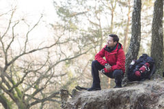 Full length of male hiker crouching on cliff in forest Stock Photo