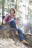 Full length of male hiker looking away while sitting on cliff in forest Royalty Free Stock Photos