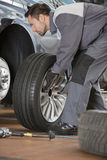 Full length of male mechanic fixing car's tire in repair shop Royalty Free Stock Images