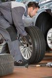 Full length of male mechanic fixing car's tire in repair shop Royalty Free Stock Image