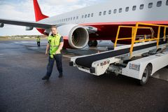 Worker Walking By Conveyor Truck With Airplane On Runway. Full length of male worker walking by luggage conveyor truck with airplane on runway stock photos