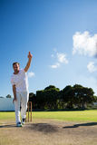 Full length of man bowling while standing on cricket field. Against sky Royalty Free Stock Photos