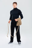Full length of man criminal burglar standing and holding rope Royalty Free Stock Photo