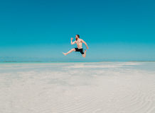 Full Length of a Man Jumping from Beach Stock Images