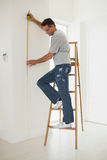 Full length of a man on ladder while measuring wall Royalty Free Stock Images