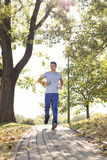 Full length of man listening music while jogging on path in park Royalty Free Stock Images
