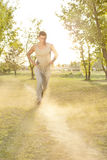 Full length of man listening music while running in park Stock Photos