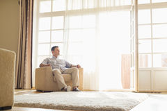 Full length of man relaxing on armchair at home Royalty Free Stock Photos