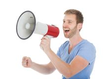 Full length of man screaming into megaphone. Over white background stock image