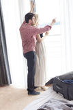Full length of man showing something to woman at window Royalty Free Stock Photos