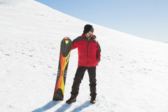Full length of a man with ski board looking away on snow. Full length of a young man with ski board looking away on snow covered landscape royalty free stock photos
