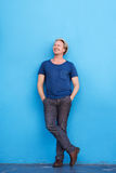 Full length man smiling against blue wall and looking away Royalty Free Stock Image