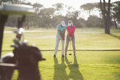 Full length of man teaching woman to play golf Stock Photos