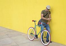 Full length of man using smart phone while standing by bicycle against yellow wall at sidewalk in city royalty free stock photo