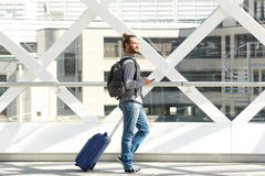 Full length man walking with suitcase and mobile phone Royalty Free Stock Photography