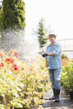 Full-length of man watering plants outside greenhouse Stock Images